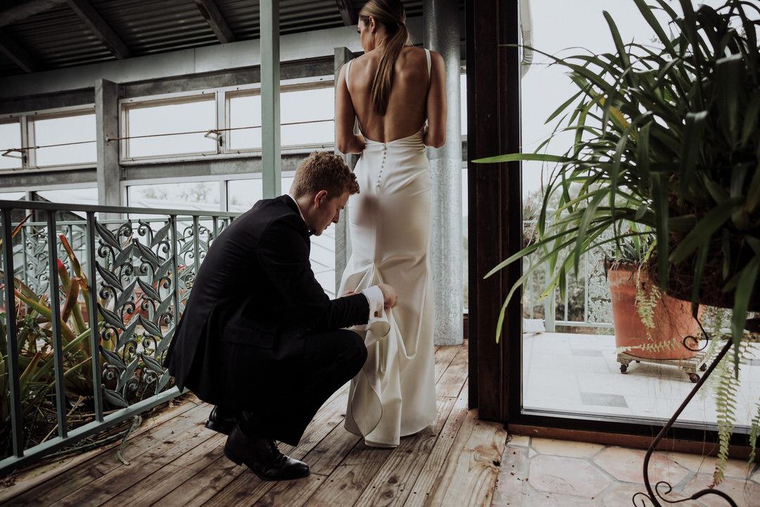 groom helping bride bustle dress