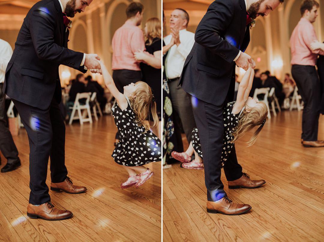 groom dancing with flower girl