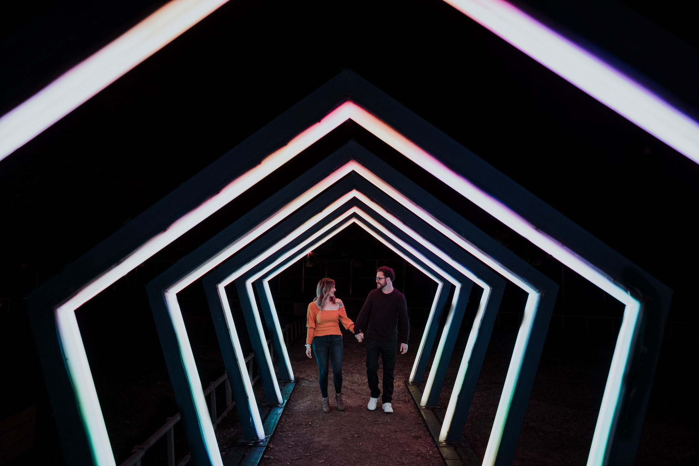couple walking down a light tunnel